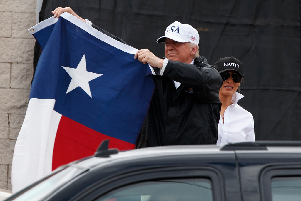 . President Donald Trump, accompanied by first lady Melania Trump, holds up a Texas flag after speaking with supporters outside Firehouse 5 in Corpus Christi, Texas, uesday, Aug. 29, 2017, , where he received a briefing on Harvey relief efforts. (AP Photo/Evan Vucci)