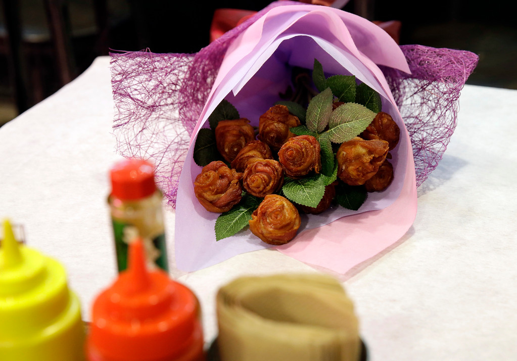 . A bouquet of edible rose shaped bacon is placed on a table at a restaurant which is offering it as part of their Valentines promotion, in Manila, Philippines on Friday, Feb. 10, 2017. A dozen edible rose shaped bacon bouquet costs P2,200 (about US$ 44) and can be delivered to love ones during Valentines Day as an alternative gift to sending real flowers. (AP Photo/Aaron Favila)