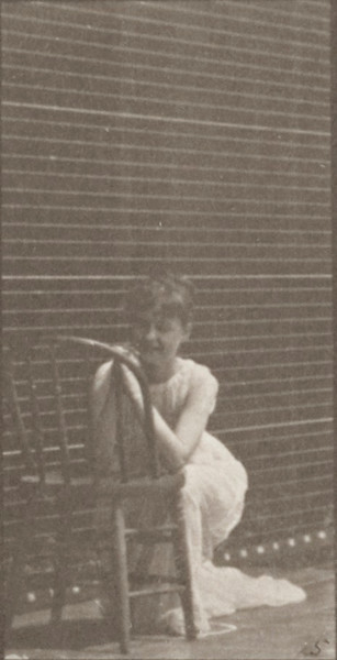 Semi-nude woman kneeling, elbows on chair and hands clasped