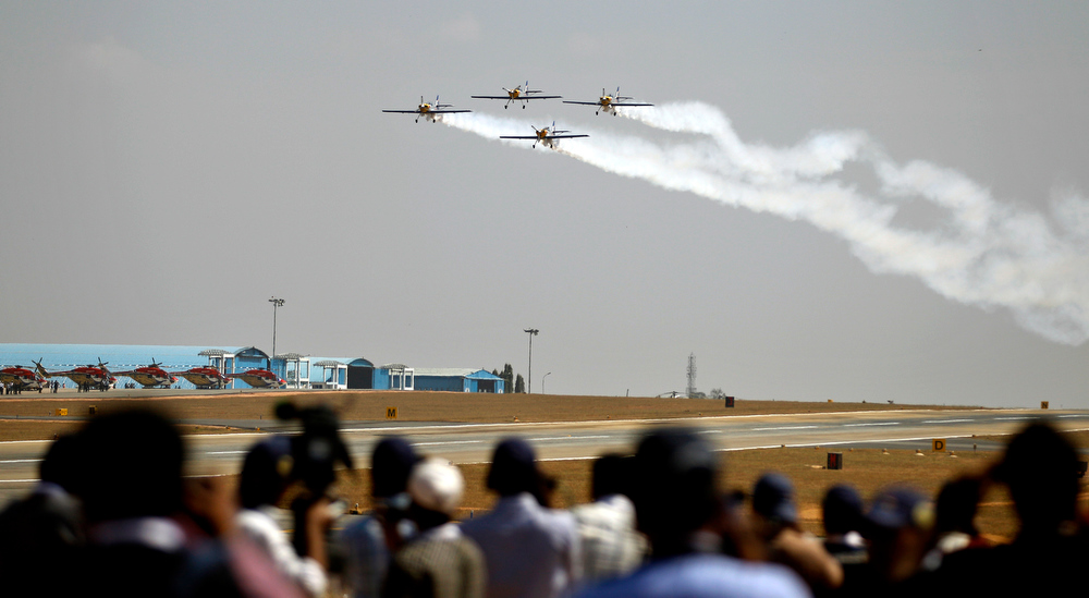 . Journalists watch the Flying Bulls Zlin 50LX single-engine and single-seater aerobatic display team from the Czech Republic perform on the opening of the Aero India 2013 at Yelahanka air base in Bangalore, India, Wednesday, Feb. 6, 2013. More than 600 aviation companies along with delegations from 78 countries are participating in the five-day event that started Wednesday. (AP Photo/Aijaz Rahi)