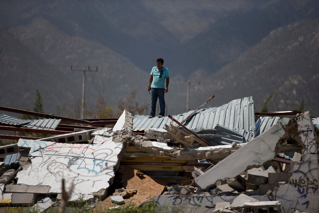 . A man stands on top of a collapsed warehouse, looking for building material to salvage after Hurricane Odile destroyed his home, in San Jose de los Cabos, Mexico, Thursday, Sept. 18, 2014. Water and electricity service remained out and phone service was intermittent. Electric commission officials said some 2,500 power poles were toppled by Odile, which struck late Sunday as a Category 3 storm. (AP Photo/Dario Lopez-Mills)
