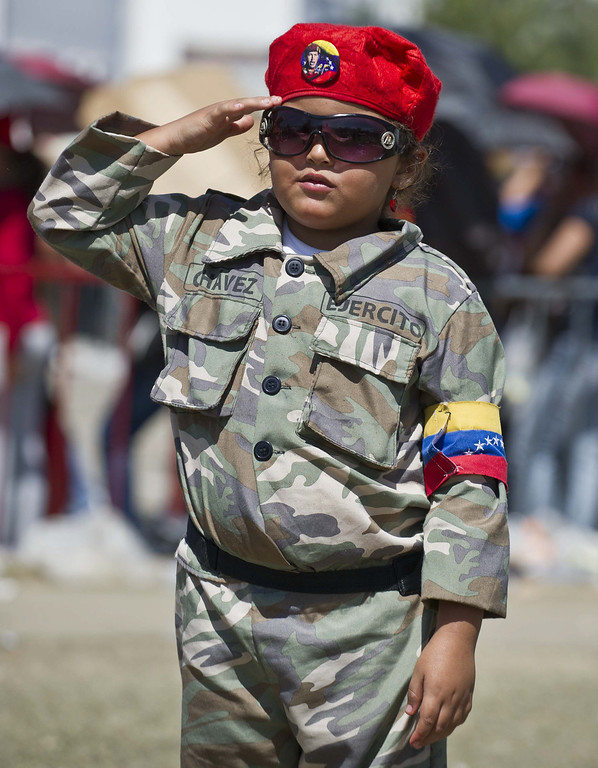 . A little girl wearing a battledress salutes outside of late Venezuelan President Hugo Chavez funeral in Caracas, on March 8, 2013. AFP PHOTO/Ronaldo  Schemidt/AFP/Getty Images