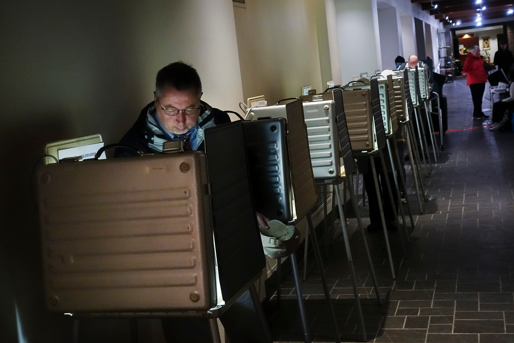 . Voters fill out their ballots at a polling station, Tuesday, Nov. 7, 2017, in downtown Cincinnati. Ohio voters will decide ballot issues on Tuesday that would place limits on drug prices and expand victims\' rights in criminal proceedings, along with several mayoral races. (AP Photo/John Minchillo)