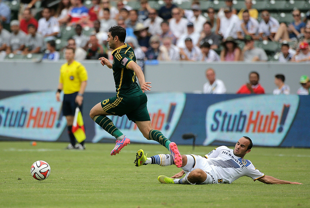 . Los Angeles Galaxy\'s Landon Donovan, right, tackles Portland Timbers\' Diego Valeri, of Argentina, during the first half of an MLS soccer match on Saturday, Aug. 2, 2014, in Carson, Calif. (AP Photo/Jae C. Hong)