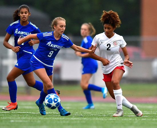 9/12/2019 Mike Orazzi | StaffrConard High School's Isabela Glynn (2) and Plainville's Michelle Gryczewski (9) on Thursday.