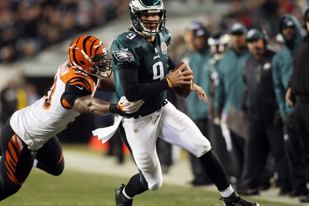 Description of . Philadelphia Eagles quarterback Nick Foles avoids the sack from  Cincinnati Bengals defensive end Michael Johnson during an NFL football game at Lincoln Financial Field in Philadelphia, Pa, Thursday, Dec. 13, 2012.  (AP Photo/The News Journal,Daniel Sato)