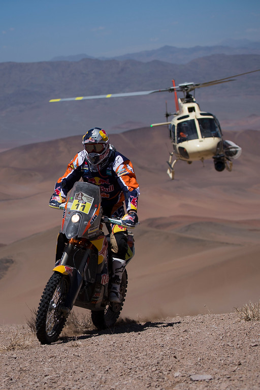 . KTM rider Ruben Faria, from Portugal, races during the fourth stage of the Dakar Rally 2015 between Chilecito, Argentina and Copiapo, Chile, as a helicopter used by organizers flies behind on Wednesday, Jan. 7, 2015. The race will finish on Jan. 17, passing through Bolivia and Chile before returning to Argentina where it started. (AP Photo/Felipe Dana)