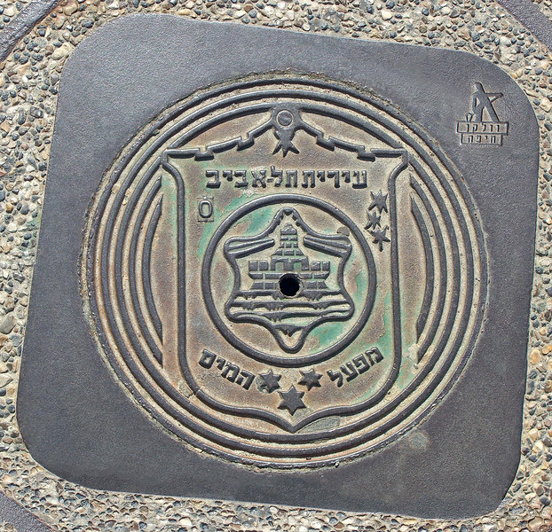 "City seal on manhole along promenade. ""Municipality of Tel-Aviv; Water Department."" Under the laborer on upper right: ""Wilkin, Haifa."""