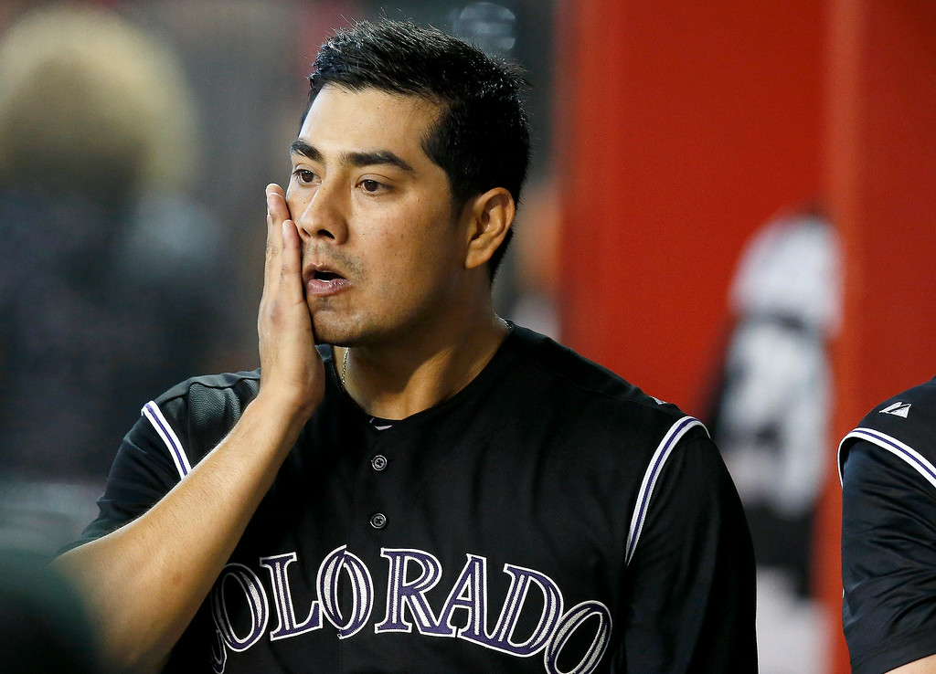 . Colorado Rockies pitcher Jorge De La Rosa wipes his face in the dugout after giving up a run to the Arizona Diamondbacks during the third inning of a baseball game Sunday, Aug. 31, 2014, in Phoenix. (AP Photo/Ross D. Franklin)