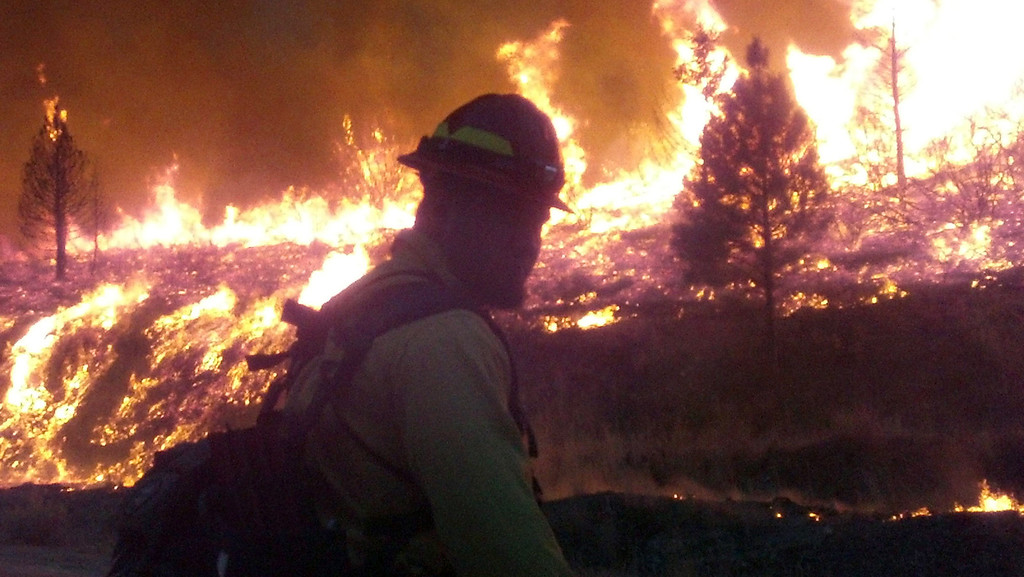 . In this photo released by the U.S. Forest Service Wednesday, Aug. 14, 2013, firefighters stand watch near the perimeter of the Elk Complex fire near the small mountain community of Pine, Idaho, Monday, Aug. 12, 2013.   (AP Photo/U.S. Forest Service)