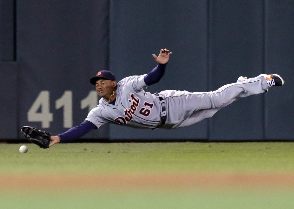 . Detroit Tigers center fielder Ezequiel Carrera makes a futile attempt for a grounder as Minnesota Twins\' Kurt Suzuki doubles to send in the tying run in the ninth inning of a baseball game, Tuesday, Sept. 16, 2014, in Minneapolis. The Twins won 4-3 with a walk-off single by Aaron Hicks. (AP Photo/Jim Mone)