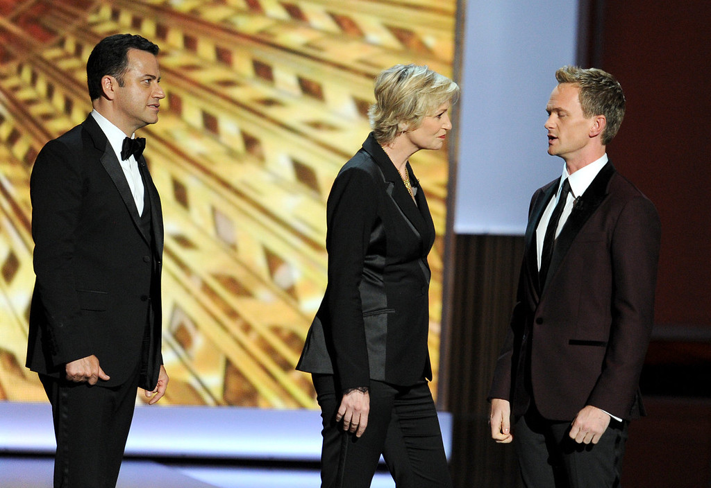 . (L-R) Tv host Jimmy Kimmel, actress Jane Lynch, and host Neil Patrick Harris speak onstage during the 65th Annual Primetime Emmy Awards held at Nokia Theatre L.A. Live on September 22, 2013 in Los Angeles, California.  (Photo by Kevin Winter/Getty Images)