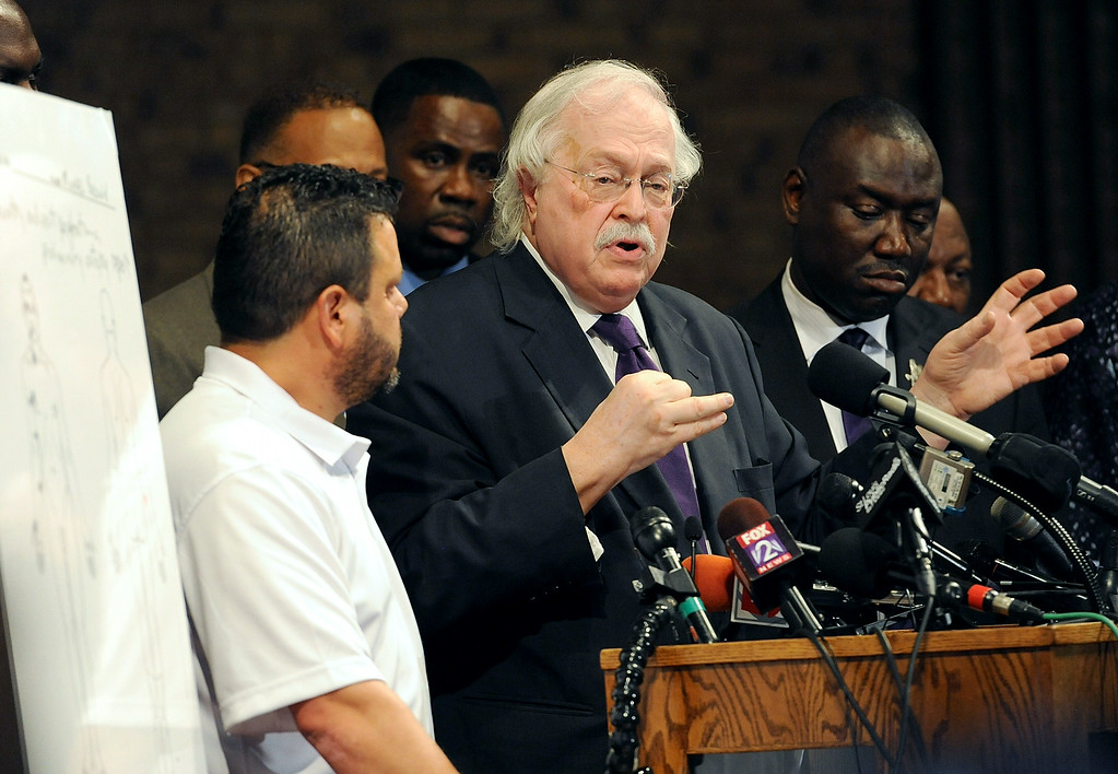 """. Forensic pathologist Michael Baden(C) addresses members of the media concerning the preliminary autopsy report of slain 18 year-old Michael Brown on August 18, 2014 at the Greater St. Marks Family Church in Ferguson, Missouri. Michael Brown, the black teen whose killing by a Missouri police officer has prompted more than a week of unrest, was shot at least six times, pathologists retained by his family said Monday. \""""Six bullets struck, and two may have re-entered\"""" the 18-year-old\'s body, said Michael Baden, tasked by Brown\'s family and lawyers to conduct an independent examination on his remains. One of the bullets hit the top of Brown\'s head, another struck his eye, while others were located on his right arm, Baden told a press conference.  AFP PHOTO / Michael B. Thomas/AFP/Getty Images"""