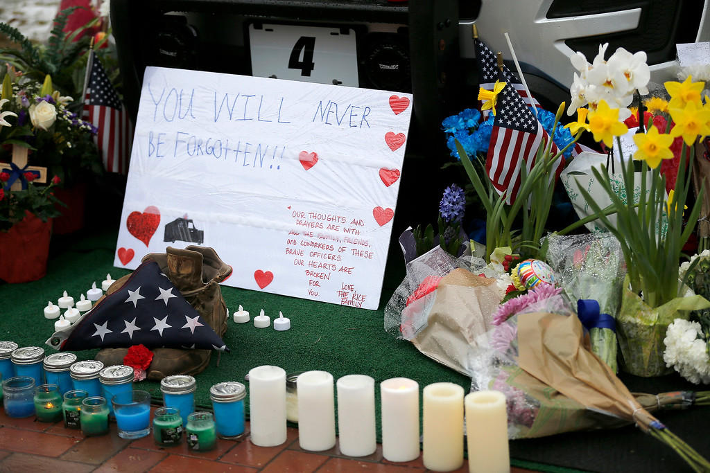 . Mourners gather and leave flowers on a police cruiser parked in front of City Hall in Westerville, Ohio, on Sunday, Feb. 11, 2018. Westerville police officers Anthony Morelli and Eric Joering were killed in the line of duty Saturday when a suspect opened fire on them as they responded to a call at a residence.(Sam Greene/The Cincinnati Enquirer via AP)