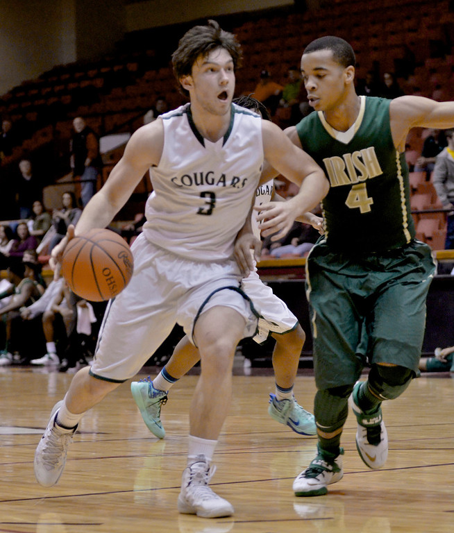 . Jeff Forman/JForman@News-Herald.com Brett Nalepa, Lake Catholic,  drives down court as Josh Williams defends in the fourth quarter of the Cougars\' 68-52 Division II regional semifinal loss March 13 to St. Vincent St. Mary at the Canton Civic Center.