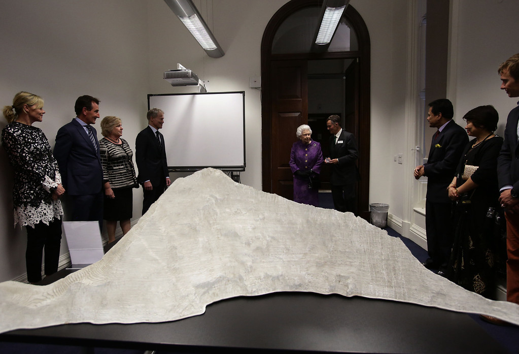 . LONDON - MAY 29: Queen Elizabeth II, accompanied by Henry Day (6th L), Chairman of the Mount Everest Foundation, is shown a model of the mountain, at a reception to celebrate the 60th Anniversary of the ascent of Everest, at the Royal Geographical Society in Kensington, on May 29, 2013 in west London, England. (Photo by Yui Mok - WPA Pool/Getty Images)