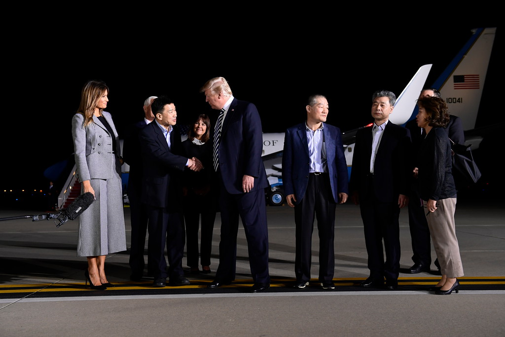 . President Donald Trump, center left, shakes hands with Tony Kim, with Kim Dong Chul, fourth right, and Kim Hak Song, third right, three Americans detained in North Korea for over a year, as they arrive at Andrews Air Force Base in Md., Thursday, May 10, 2018. First lady Melania Trump, far left, Vice President Mike Pence, behind Tony Kim, and his wife Karen Pence, behind Trump, and Secretary of State Mike Pompeo, far right, were also at the air force base to greet them. The woman at right is unidentified. (AP Photo/Susan Walsh)