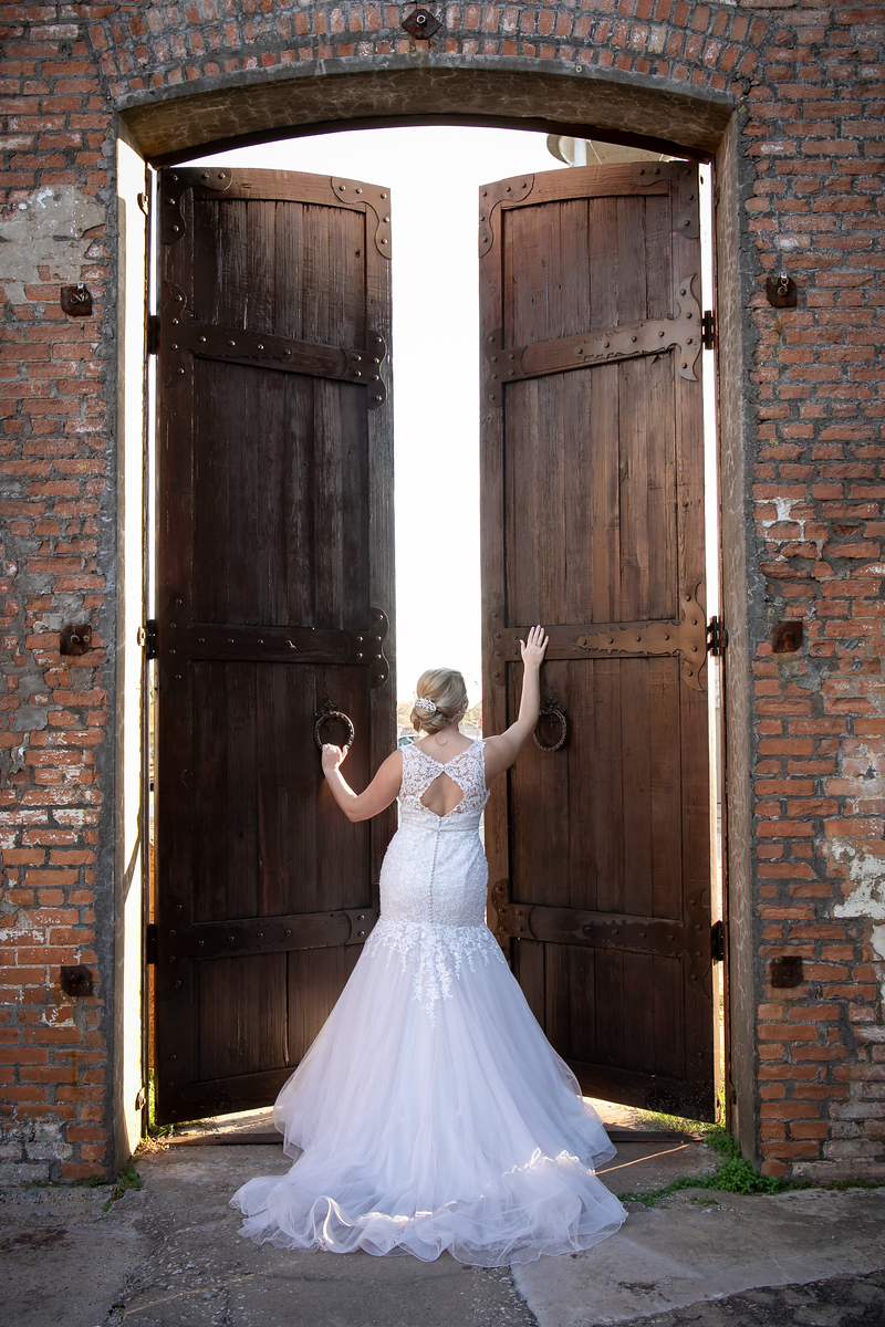 bride opening large wooden doors that lead to the wedding ceremony space