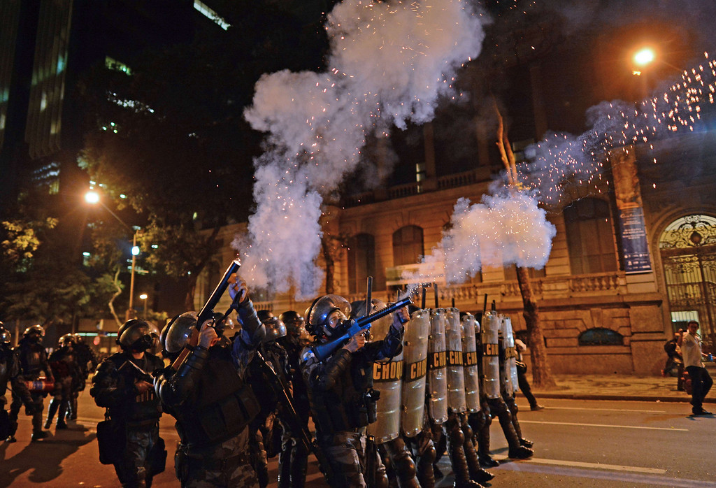". Riot police officers fire tear gas at violent demonstrators after clashes erupted following a march by Brazilian workers in Rio de Janeiro on July 11, 2013 in a day of industrial action called by major unions to press demands for better work conditions. Demonstrators on Thursday blocked roads and staged protest rallies across the country on the ""National Day of Struggles\"" which was called by the country\'s five leading labour federations during last month\'s mass street protests to demand better public services and an end to endemic corruption. CHRISTOPHE SIMON/AFP/Getty Images"