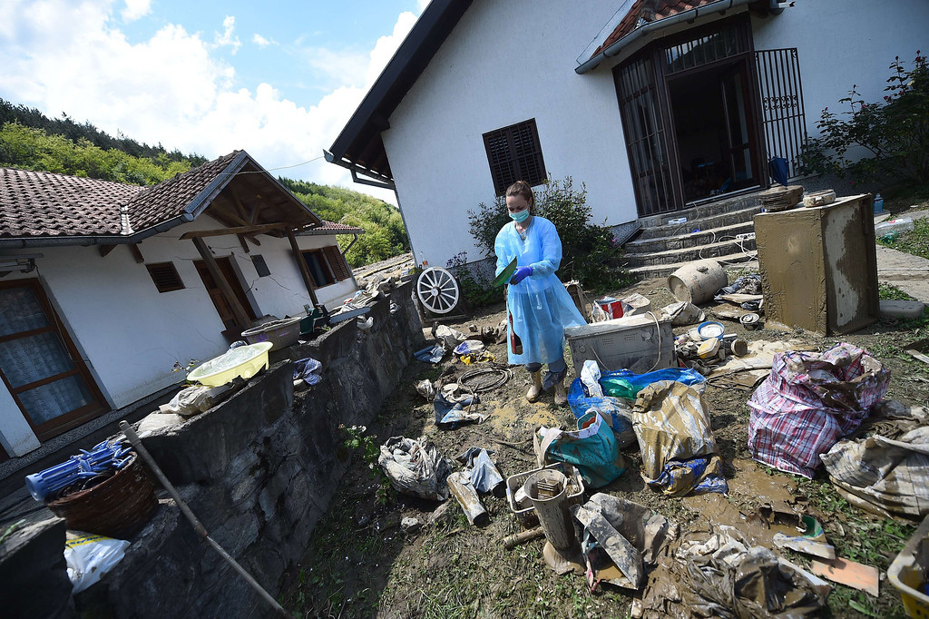. A woman wearing protective gear sorts personal belongings outside her flooded house in Krupanj, some 130 kilometres south west of Belgrade, on May 20, 2014, after the western Serbian town was hit with floods and landslides, cutting it off for four days. Serbia declared three days of national mourning on May 20 as the death toll from the worst flood to hit the Balkans in living memory rose and health officials warned of a possible epidemic.   AFP PHOTO / ANDREJ ISAKOVIC/AFP/Getty Images