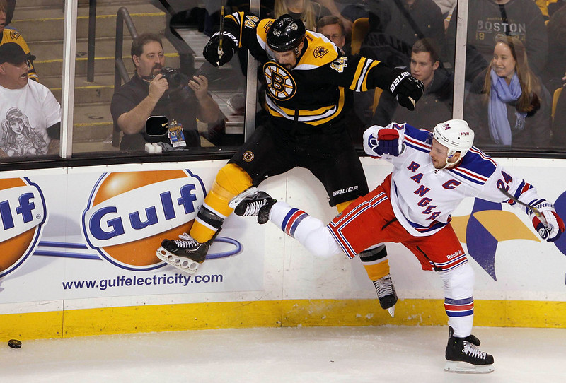 . Boston Bruins\' Dennis Seidenberg competes for the puck with New York Rangers\' Ryan Callahan (R) during the first period of their NHL ice hockey game at TD Garden in Boston, Massachusetts January 19, 2013. REUTERS/Jessica Rinaldi