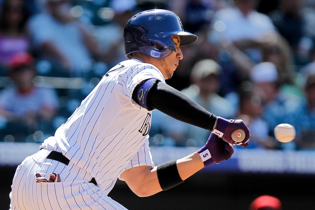 . Colorado Rockies\' Carlos Gonzalez makes an unsuccessful bunt during the eighth inning of a baseball game against the Arizona Diamondbacks, Wednesday, May 22, 2013, in Denver. Gonzalez hurt his left index finger on the play but the Rockies won 4-1. (AP Photo/Barry Gutierrez)