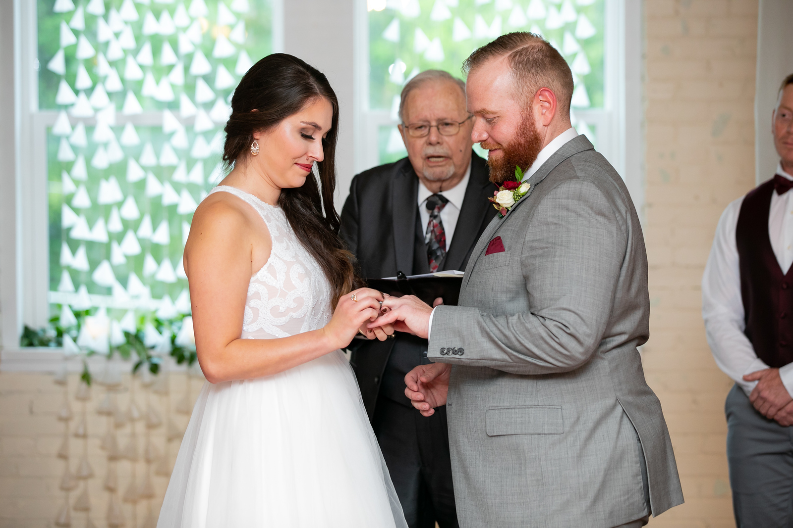 bride wearing a simple and shear modern wedding dress slipping a wedding ring on her groom wearing a grey suit as they wed