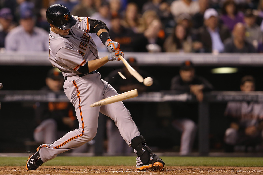 . Buster Posey #28 of the San Francisco Giants breaks his bat as he hits into a double play and collects an RBI against the Colorado Rockies in the third inning at Coors Field on April 21, 2014 in Denver, Colorado.  (Photo by Doug Pensinger/Getty Images)