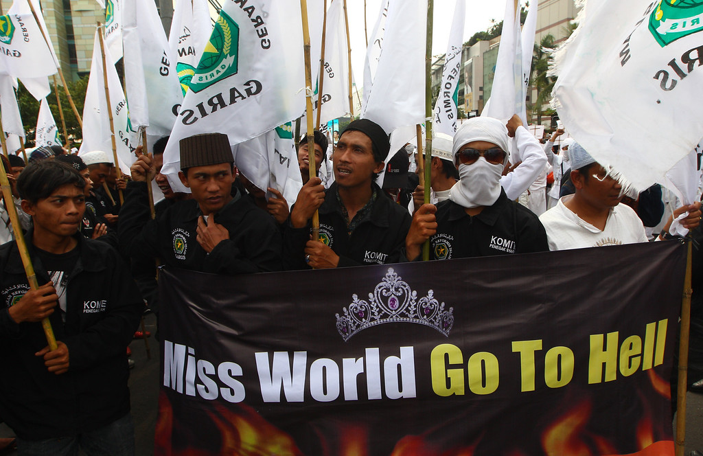 . In this Friday, Sept. 6, 2013 photo, Muslim men display a banner during a protest demanding the cancellation of the Miss World pageant, in Jakarta, Indonesia, Friday, Sept. 6, 2013. (AP Photo/Dita Alangkara)