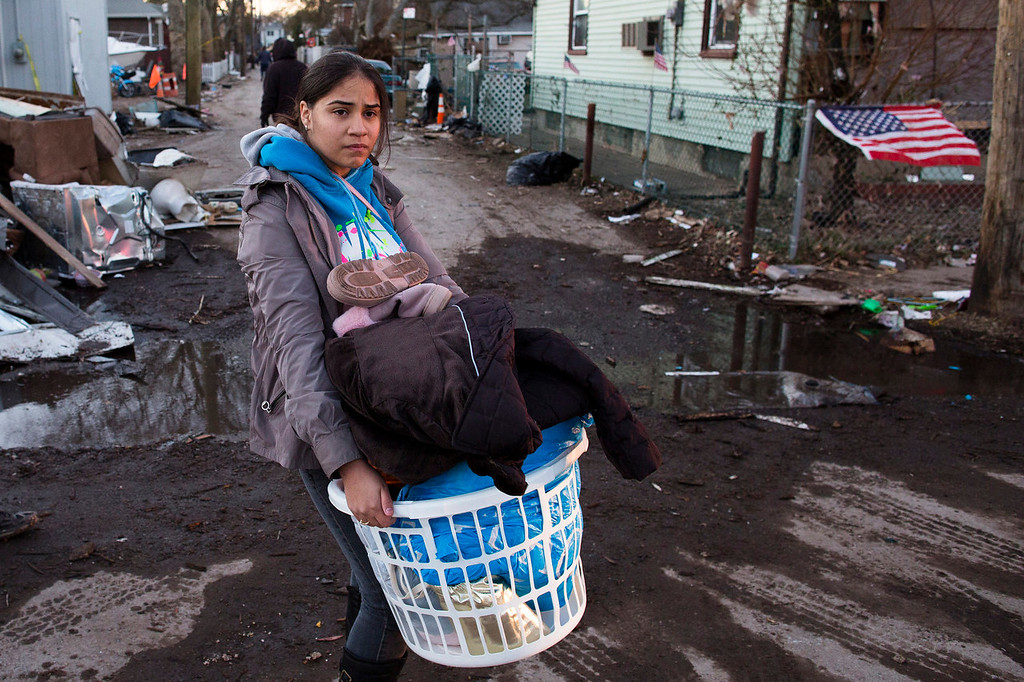 . A resident of Staten Island\'s New Dorp Beach neighborhood carries a basket full of clothes and other items on her street that was devastated by Superstorm Sandy, Monday, Nov. 5, 2012, in New York. Although many areas of the metropolitan area are beginning to return to normal, neighborhoods of Staten Island\'s southern shore remain without power as the cleanup continues. (AP Photo/ John Minchillo)
