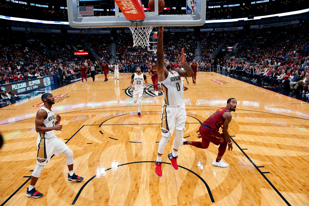 . New Orleans Pelicans forward DeMarcus Cousins (0) drives to the basket in front of Cleveland Cavaliers guard JR Smith in the first half of an NBA basketball game in New Orleans, Saturday, Oct. 28, 2017. (AP Photo/Gerald Herbert)