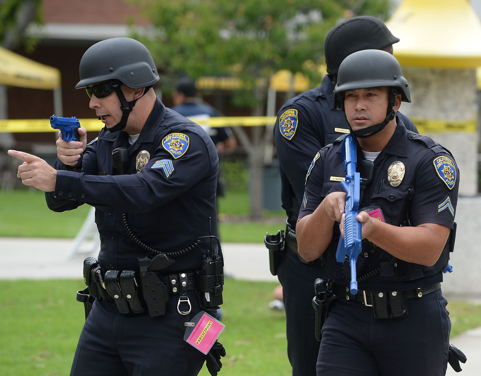 . A multi-agency response exercise to an active shooter and mass casualty incident was held Tuesday on the Cal State Long Beach campus. First responding campus police officers move across the campus looking for shooter with fake weapons drawn. 20130813 Photo by Steve McCrank / Staff Photographer