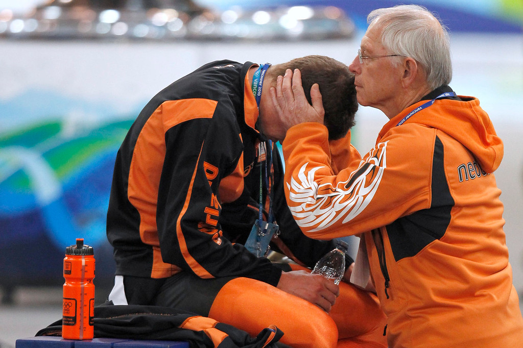 . Netherlands\'s Sven Kramer, left, is comforted after he was disqualified during the men\'s 10,000 meter speed skating race at the Richmond Olympic Oval at the Vancouver 2010 Olympics in Vancouver, British Columbia, Tuesday, Feb. 23, 2010. Lee Seung-hoon of South Korea won a stunning gold medal in men\'s 10,000-meter speedskating Tuesday when overwhelming favorite Sven Kramer made an amateurish mistake, failing to switch lanes just past the midway point of the race, and was disqualified. (AP Photo/Kevin Frayer)