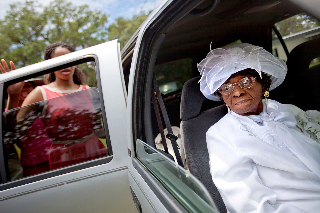 . Cathleen Hillary, 93, the oldest resident of Sapelo Island, Ga. leaves a church service with her great granddaughter Milaika Ellison, for the 129th anniversary of St. Luke Baptist Church on the island on Sunday, June 9, 2013. (AP Photo/David Goldman)