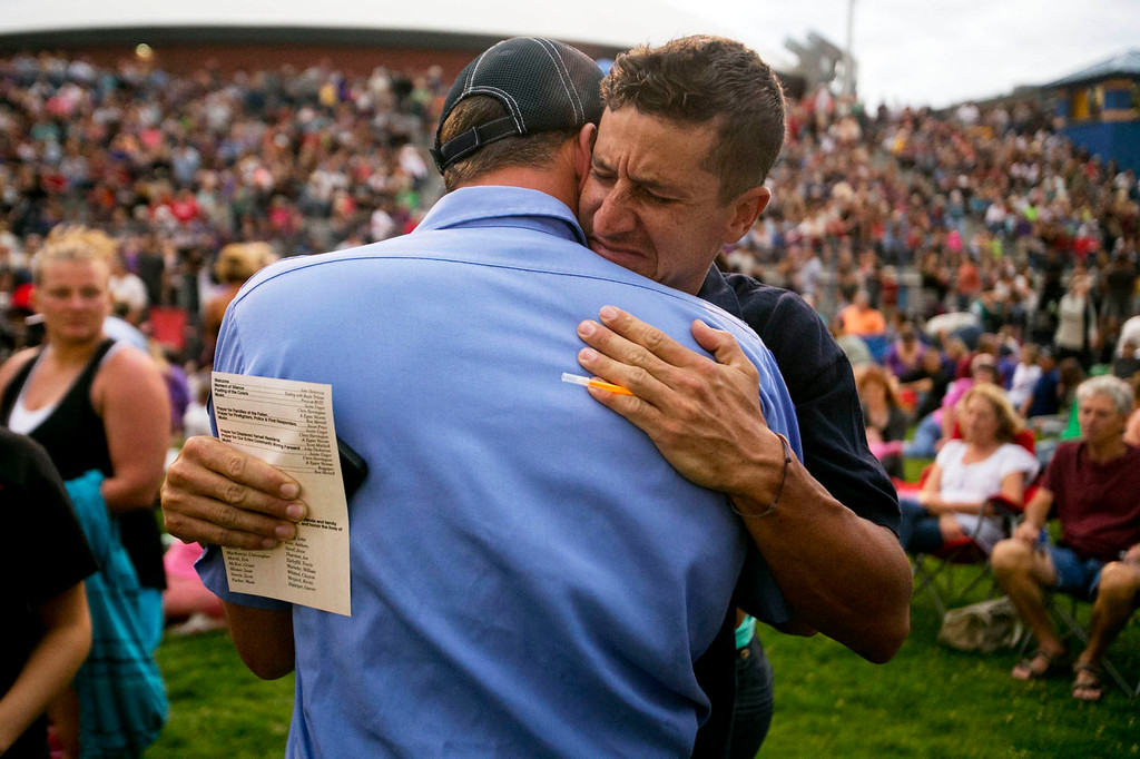 . Cooper Carr, right, a Sedona Firefighter and formerly of the Prescott Hot Shots, hugs Prescott Fire Captain Kevin Keith during a vigil for the 19 firefighters killed battling the Yarnell Hill Fire, on the football field at Prescott High School in Prescott, Ariz. on Tuesday, July 2, 2013. (AP Photo/The Arizona Republic, David Wallace)
