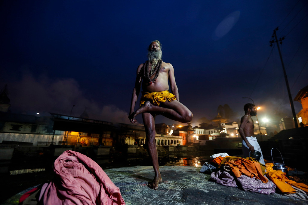 . A Sadhu (holy man) attends early morning prayers standing on one leg at the Pashupati Temple in Kathmandu, Nepal, 27 February 2014, to mark the biggest Hindu festival Maha Shivaratri. More than 100,000 Hindu devotees including Sadhus from across the country and neighboring India are worshipping at the Pashupati temple to celebrate the birthday of Lord Shiva, the god of creation and destruction. Hindus mark the Maha Shivratri festival by offering special prayers and fasting.  EPA/NARENDRA SHRESTHA