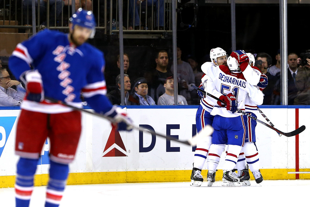 . Francis Bouillon #55 of the Montreal Canadiens celebrates with his teammates Rene Bourque #17 and David Desharnais #51 after scoring a goal in the second period against Henrik Lundqvist #30 of the New York Rangers during Game Four of the Eastern Conference Final in the 2014 NHL Stanley Cup Playoffs at Madison Square Garden on May 25, 2014 in New York City.  (Photo by Elsa/Getty Images)