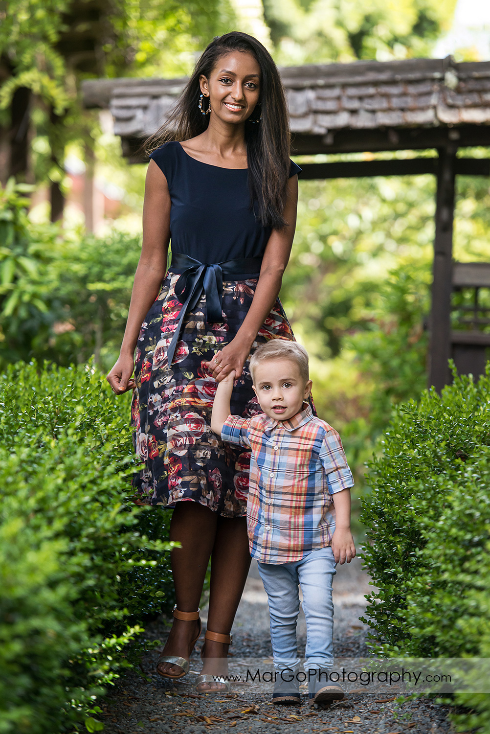 woman in navy blue dress and little boy walking among greenery in Shinn Historical Park and Arboretum in Fremont