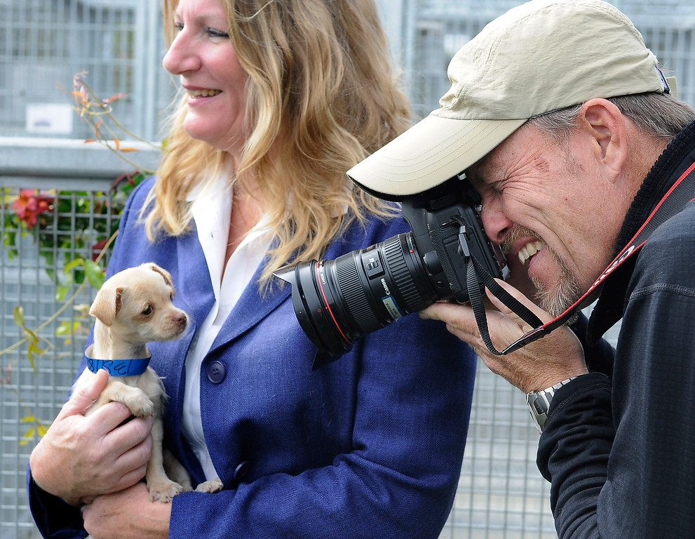 . LA Times photographer Al Seib photographs a puppy in the arms of Jan Selder, who is the Director of LA City Animal Services. The South Los Angeles Animal Services Center officially opened today at 1850 West 60th Street. Mayor Antonio Villaraigosa and other city officials cut a ribbon and went on tours to see the state of the art facility that showcases animals in a way that is humane, clean and allows pets to meet potential new families. The outdoor kennels reduce disease transmission and noise, while other animals like rabbits and reptiles are given more prominence in the location where they are viewed.  Los Angeles, CA 4/4/2013(John McCoy/Staff Photographer