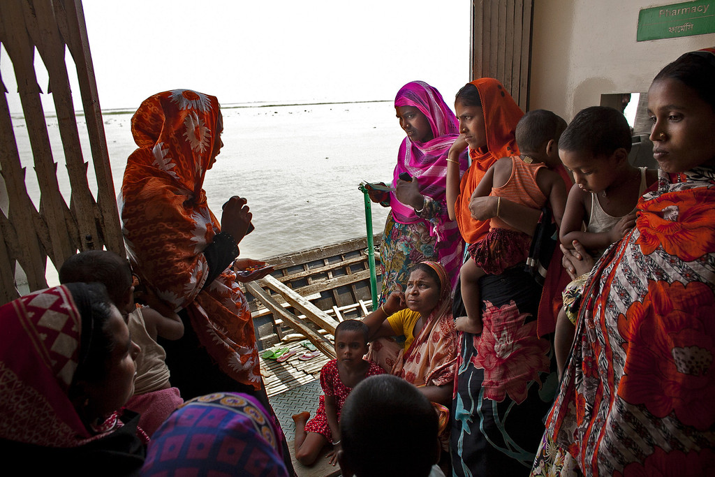 """. Women from the Modafot village wait for treatment at the Emirates Friendship Floating Hospital May 19, 2014 in the Chilmari district, Bangladesh. Friendship floating hospitals dock for up to 5 months at remote islands, or \""""chors\"""", in the north of Bangladesh with a full medical team and stocked pharmacy, providing health care at affordable cost. (Photo by Allison Joyce/Getty Images)"""