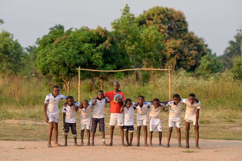"""The opposing team, also from the CFS, wearing white World Vision-provided uniforms, poses by their goal. Grace Mukoma, 10  yr-old boy, loves to play soccer football at  the World Vision Child Friendly Space near his home in Central Kasai Province, Kananga, DRC.  What Grace really loves to do is to go to the Tshilumba Child Friendly Space. It is 2 buildings surrounded by palm trees – out back there's a row of 8 latrines built by WV. There are about 40 kids outside. The morning light is soft on the tall grass. Kids are dancing and doing some fun gymnastics/acrobatics. Grace is small but energetic. He has a nice smile and love to show off how limber he is. He bends and twists, does backflip. Kids form a circle, Grace dances in the middle – most are barefoot in the soft, brown sand. Three boys, Grace, Seba and Kabasela, Grace's best friend, do an acrobatic act that involves the three of them hooked together. Grace loves dancing.   Grace - """"I feel at ease when I'm dancing with my friends and most importantly, it makes me forget about the war.""""  """"When I'm dancing among my friends, I feel very happy and I forget the past.""""  When I'm dancing, I'm not alone. I forget all the things during the war.""""  Background Grace lives with his widowed mom, Mbombo Elize, sister Harriet, 7, and an extended family of relatives, including his widowed grandmother, Kapinga Godelive, 66.  Mbombo has had 4 children, the first when she was 15. 2 died during the time they had to run away because of the war. Now it's just Grace and his sister Harriet, 7.  They live in the Kasai Centrale province in a place called Katoka. It's a rural community. Grace and his family had to run when war broke out in the DRC.  His father was killed. His mother and her 4 children ran about 2 kilometers down the road from his house towards the Lualua River. They hid there for about 3 months. Unfortunately, because of a lack of food and disease, Grace's brother and a sister died. After about 3 months Grace and his family"""