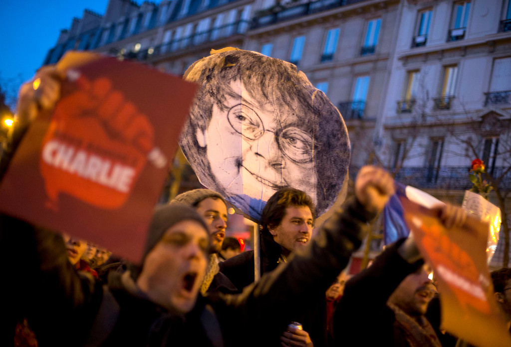. People demonstrate on Republique square with  a portrait of slain Charlie Hebdo cartoonist Jean Cabut known as Cabu, during the demonstration in Paris, France, Sunday, Jan. 11, 2015. Hundreds of thousands of people marched through Paris on Sunday in a massive show of unity and defiance in the face of terrorism that killed 17 people in France\'s bleakest moment in half a century. (AP Photo/Peter Dejong)