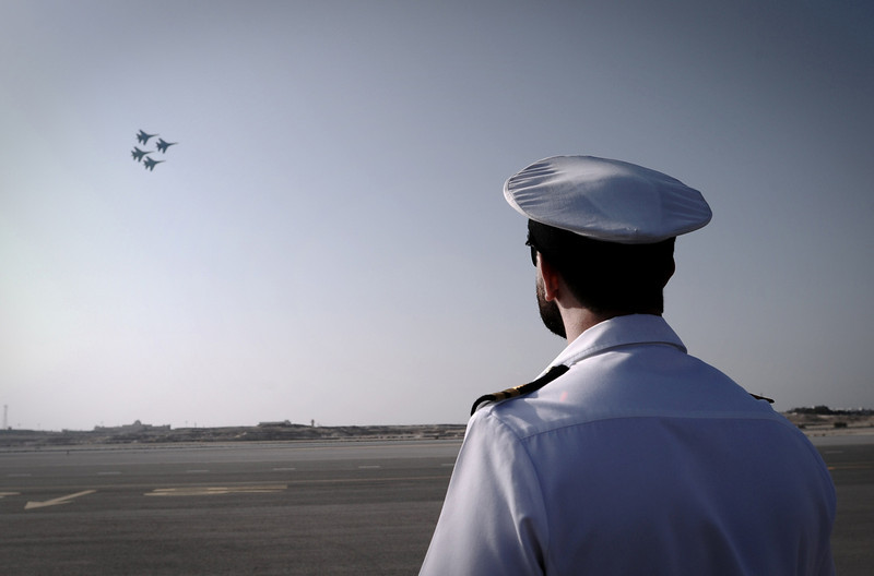. A pilot watches the Russian Knights display team perform during the opening of the Bahrain International Airshow 2014, in Sakhir, south of the capital Manama, on January 16, 2014. (MOHAMMED AL-SHAIKH/AFP/Getty Images)