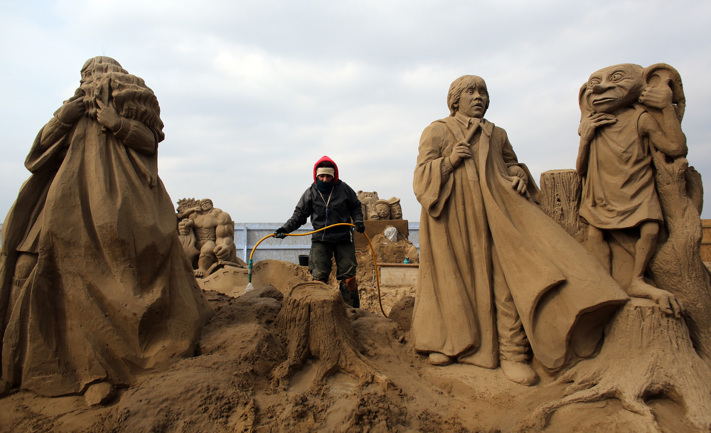 . A sand sculptor works on a Harry Potter themed sand sculpture as pieces are prepared as part of this year�s Hollywood themed annual Weston-super-Mare Sand Sculpture festival on March 26, 2013 in Weston-Super-Mare, England. Due to open on Good Friday, currently twenty award winning sand sculptors from across the globe are working to create sand sculptures including Harry Potter, Marilyn Monroe and characters from the Star Wars films as part of the town\'s very own movie themed festival on the beach.  (Photo by Matt Cardy/Getty Images)