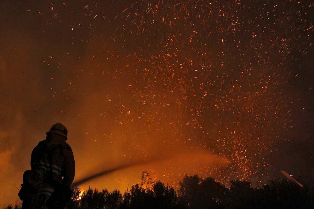 . A firefighter douses embers from the Springs Fire at Point Mugu State Park, May 3, 2013.  REUTERS/Jonathan Alcorn