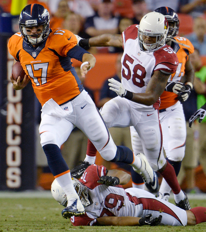 . Brock Osweiler (17) of the Denver Broncos evades a tackle by David Carter (79) of the Arizona Cardinals during the last pre-season game of the season at Sports Authority Field at Mile High. August 29, 2013 Denver, Colorado. (Photo By Joe Amon/The Denver Post)