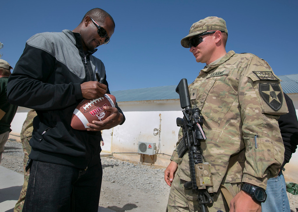 . Denver Broncos cornerback Champ Bailey autographs a football for a soldier stationed in the Middle East during a stop on his week-long USO/NFL tour March 17, 2013.   USO Photo by Fred Greaves