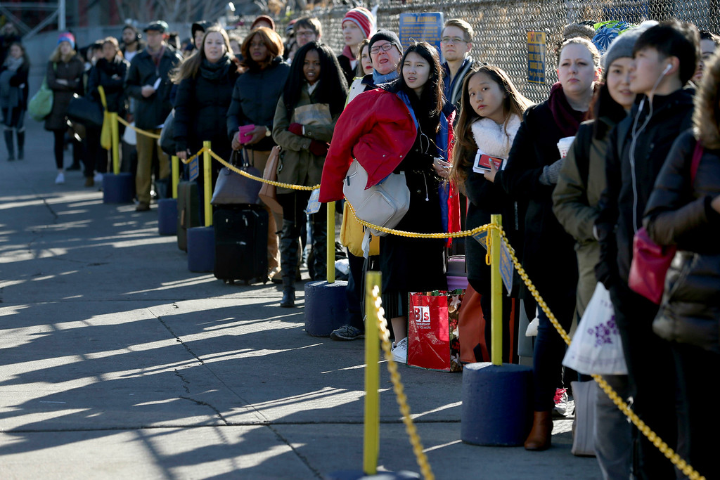 . Travelers wait in line to board buses in New York, Wednesday, Nov. 23, 2016. Almost 49 million people are expected to travel 50 miles or more for the Thanksgiving holiday, the most since 2007, according to AAA. (AP Photo/Seth Wenig)