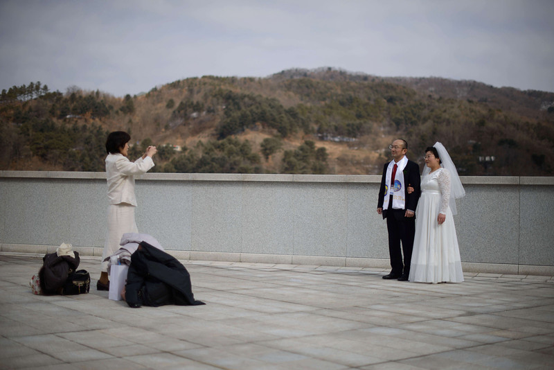 ". A newly-wed couple pose for photos following a mass wedding event held by the Unification Church in Gapyeong on February 12, 2014. Unification Church members forming 2500 couples from 52 countries were married in a mass wedding in South Korea -- only the second such event since the death of their ""messiah\"" and controversial church founder Sun Myung Moon. (ED JONES/AFP/Getty Images)"