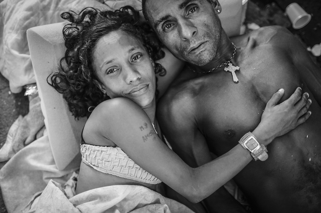 . Couple Eduardo and Michelle pose while lying together on the sidewalk in the Centro neighborhood on March 23, 2015 in Rio de Janeiro, Brazil. Michelle said she has lived in the streets since she was 7 years old. A Rio government report from 2013 stated that 5,500 people live on the streets in Rio, not including those who live in shelters or lack stable housing. Close to 40 percent of the street dwellers in the study were found to lack identification, limiting their access to public services. (Photo by Mario Tama/Getty Images)
